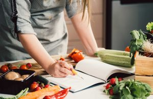 Woman Looking over Plant-Based Cookbooks
